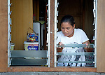 Aida Encarnacion places glass panes in the windows of her temporary home in Tolosa, a city in the Philippines province of Leyte that was hit hard by Typhoon Haiyan in November 2013. The storm was known locally as Yolanda. Christian Aid and other members of the ACT Alliance are working here and throughout the affected region to help people recover and rebuild in the wake of the massive storm.