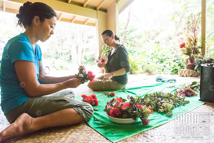 Two women weave kupe'e (wrist or ankle adornments) out of 'ohi'a lehua flowers and fern leaves, Volcano, Big Island.