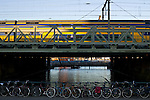 A train pulls into Amsterdam Central Station with typical Amsterdam bikes in the foreground.