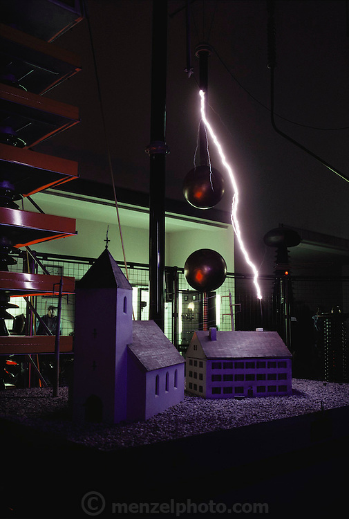 Lightning demonstration strikes model house and church with impulses of up to 800,000 volts. Deutsches Museum, Munich, Germany. 1991..Lightning occurs when a large electrical charge builds up in a cloud, probably due to the friction of water and ice particles. The charge induces an opposite charge on the ground, and a few leader electrons travel to the ground. When one makes contact, there is a huge backflow of energy up the path of the electron. This produces a bright flash of light, and temperatures of up to 30,000 degrees Celsius.