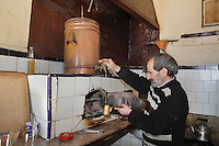 Man making traditional mint tea with a samovar of hot water heated over a wood fire, in a cafe in the medina of Tetouan, on the slopes of Jbel Dersa in the Rif Mountains of Northern Morocco. The medina of Tetouan dates to the 16th century and was declared a UNESCO World Heritage Site in 1997. Picture by Manuel Cohen