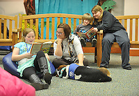 NWA Democrat-Gazette/Michael Woods --01/14/2015-- w @NWAMICHAELW... Elizabeth Becker, age 10, (left) reads a book to Erin Renollet Children's Assistant with the Springdale Public Library and Banjo, a therapy dog, along with Gabriel Stewart, age 4, and his mother Kristie Stewart (right) during Wednesday evenings session of the Kibbles and Books program at the Springdale Public Library. Kibbles & Books is a literacy program designed to build confidence in young readers by reading out loud to therapy dogs giving the children a chance to practice their literacy skills in a stress-free and fun context.