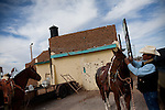 From left, Roy Aparicio, 58, and Elias Reyes, 50, both of Hath New Mexico prepare their horses for a parade in Columbus, New Mexico. Recently federal authorities arrested the mayor, police chief, and trustees who were allegedly operating an illegal gun running ring.