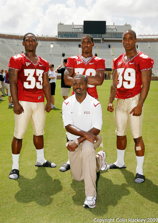 TALLAHASSEE, FL. 8/9/09-FSU-RUNNING BACKS 0809 CH01-Florida State Running Backs Coach Dexter Carter, kneeling, poses with running backs Ty Jones, left, Jermaine Thomas, and Tavares Pressley, right,  during media day Sunday in Tallahassee...COLIN HACKLEY PHOTO