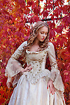 Young woman with curly blonde hair looking down wearing period regency costume standing outdoors beside red autumn leaves