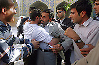 President Mahmoud Ahmdinejad's anxious bodyguard stays close as a supporter embraces the Iranian leader following one of his speeches in the central Iranian town of Isfahan (Esfahan). The bodyguards are banned from stopping, or separating ordinary people from the Iranian president if they go towards him as part of his populist policy of being approachable and in touch with the people.