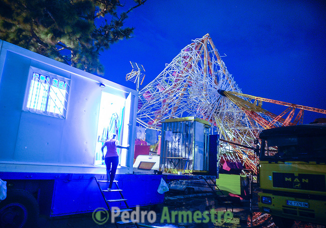 A woman walks under the wreckage of a fair ride after a tornado ripped through a funfair in Gandia, near Valencia on September 29, 2012.  At least eight people, including a young girl and an elderly woman, have died in Spain as a result of floods brought on by downpours, regional officials said. Four people died in the Andalusia region, including a woman in her 80s, a couple found in their car and a man who died of a heart attack. Some 500 people remained evacuated from their homes in the area early on Saturday after the torrential rains caused rivers to break their banks and flooded roads and railways, regional authorities said. © Pedro ARMESTRE