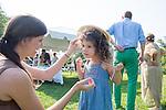 Teacher Veronica Urbanik helps Talia Siegel adjust the hat that she made for the Child Development Center's annual garden party. Photo by Ben Siegel/ Ohio University
