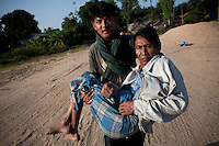 A Burmese refugee carries a family member to a boat to take them both back across the Moe Me river to Burma. After less than three days in Thailand the Burmese refugees had begun to return home. An estimated 20,000 had fled into Thailand to escape clashes in the border towns of Myawaddy and Pyaduangsu, only a day after a Burmese election which critics described as a sham..Ethnic minorities along the Thai-Burma border had warned earlier that the junta would launch a major offensive after the election, as many armed rebel groups had refused to become part of the government-controlled Border Guard Forces.&nbsp;
