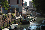 Rubbish being emptied into a barge on a venetian canal. Venice, Italy.