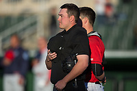 Home plate umpire Mike Rains stands for the National Anthem prior to the South Atlantic League game between the Lakewood BlueClaws and the Kannapolis Intimidators at Kannapolis Intimidators Stadium on April 8, 2017 in Kannapolis, North Carolina.  The BlueClaws defeated the Intimidators 8-4 in 10 innings.  (Brian Westerholt/Four Seam Images)