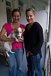 Full length portrait of Leigh and Helena outdoors with their dog on their front porch in Philadelphia<br /> <br /> Release # 2528