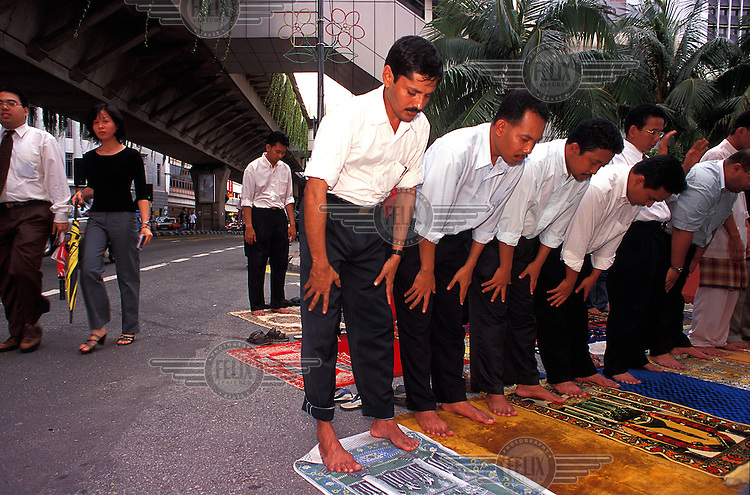 Chinese and Indian Malays walk past group of Muslim civil servants and office workers praying outside the Masjid Jamie in central Kuala Lumpur.  Credit: Chris Stowers.