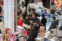"Shoppers at the Cartier perfume counter in the Macy's Herald Square flagship store in New York looking for bargains on the day after Thanksgiving, Black Friday, November 28, 2014. Many retailers, including Macy's, opened their doors on Thanksgiving evening extending the shopping day and giving Thanksgiving the nickname ""Gray Thursday"". (© Richard B. Levine)"