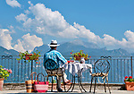 A man wearing a white hat admires the view of Lake Como while seated on a patio in Menaggio, Italy