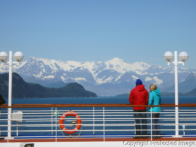 couple watched the snow capped mountains of Alaska from the deck of a cruise ship
