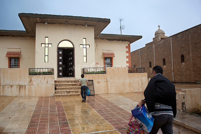 31/10/14. Alqosh, Iraq. Wassam (left) walks ahead of his uncle Salam as they walk through the gates of the orphanage, part of the Virgin Mary Monastery in Alqosh.