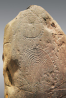 """Detail of prehistoric  petroglyphs, rock carvings, of geometric designs carved by the the prehistoric Camuni people in the Copper Age around the 3rd milleneum BC, Stele """"Bagnolo 2"""" found in 1972 from Malegno near Bangnolo Ceresolo. Museo Nazionale della Preistoria della Valle Camonica ( National Museum of Prehistory in Valle Cominca ), Lombardy, Italy. Grey Background"""