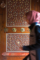 Muslim woman enters mosque by ornate carved entrance door, Suleymaniye Mosque, Istanbul, Republic of Turkey