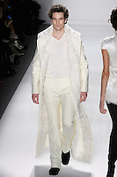 Model walks runway in a men's ivory wool felt storm coat w/curly lamb colllar, and men's ivory bamboo v-neck T's, from the Zang Toi Fall 2012 &quot;Glamour At Gstaad&quot; collection, during Mercedes-Benz Fashion Week New York Fall 2012 at Lincoln Center.