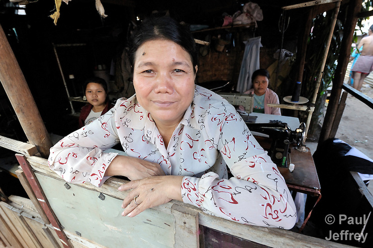 A member of a women's self-help group, Morn Nen, 48, stands in a room of her home where her two daughters sew to produce income for their family in the Phnom Penh neighborhood of Sen Rikreay. Many people in this community are infected or affected by HIV and AIDS, and Buddhist monks and other religious meet with them regularly to mediate and discuss their challenges.