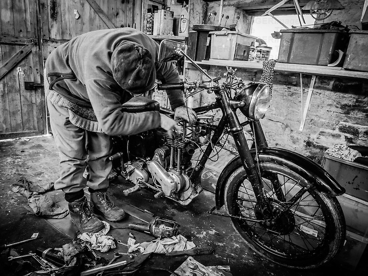Enthusiast working on a motor bike in an old workshop.