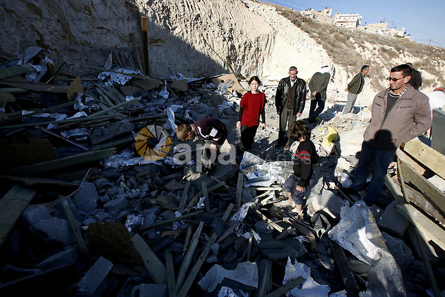 Palestinians search in the rubble of their house after it was demolished by Jerusalem municipality workers in the east Jerusalem on December 21, 2012. Palestinian homes built without a construction permit are often demolished by order of the Jerusalem municipality. Photo by Mahfouz Abu Turk
