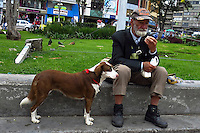 BOGOTA, Colombia. 13th June 2014. An older man shares a moment next to his dog in a street in Bogota few days before presidential election in Colombia. Photo by Eduardo Munoz Alvarez/VIEWpress