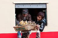 Myanmar, Burma.  Passengers on Train Buying Bananas from Platform Vendors at Kalaw Train Station.