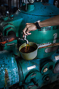 A factory worker pours out the oil for testing purpose at the Sipef oil mill in Sumatra, Indonesia.