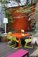 What was a dark and sombre urban courtyard has been transformed with raised decking and colourful contemporary furniture