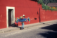 Broom vendor waling down a street in the Spanish colonial town of Antigua, Guatemala
