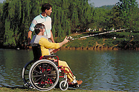 Young man in wheelchair fishing from bank of lake under the supervision of occupational therapist. Birmingham Alabama.
