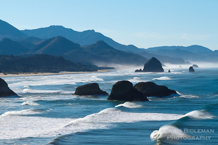 View south at Ecola Point looking at Crescent Beach towards Cannon Beach, Oregon with rolling waves on the ocean on a blue sky day.