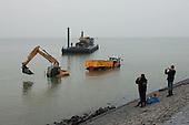 Grondverzetmachines vast op strand Harlingen