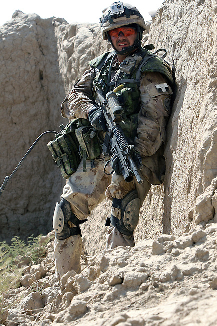 Warrant Officer Mike Saunders takes cover behind a wall during a firefight with Taliban insurgents in the village of Pashmul in Zhari district, Kandahar province, Afghanistan. Saunders is with a team of Canadian soldiers mentoring Afghan troops in Zhari, where they fight daily skirmishes with insurgents. Zhari is where the hardline Taliban movement originated in the early 1990s. Sept. 29, 2008. DREW BROWN/STARS AND STRIPES