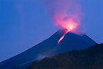 """By pre-dawn light, an """"awan panas"""" eruption on Merapi lives up to its name by glowing as a """"hot cloud"""". Incandescent lava at the volcano's summit illuminates spewing ash and gas."""
