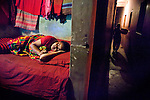 "Faridpur Brothel is the second to largest brothel in Bangladesh. (17 registered brothels in the country) 600+ girls live in a hidden neighboorhood accesible through one of the six alleyways, covered with small ragged curtains mimicking doors. Many girls are under aged - the ""legal"" age being 18. A Madame takes a nap as life around her continues. March 10, 2011. Gabriela Barnuevo"