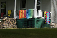 Little Lake Sunapee, New Hampshire. colorful beach towels dry on cabin porch rail after swimming activities.