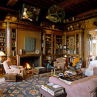 A hand-painted leather frieze runs around the ceiling of this living room and the walls are lined with shelves displaying a collection of artefacts