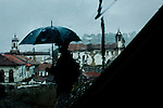 A man with an umbrella walks through the rain in Ouro Preto, Brazil.