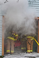 Westerville fire fighters stand in the open door of a smoke-filled garage where they extinguished a fire in a Corvette parked there.