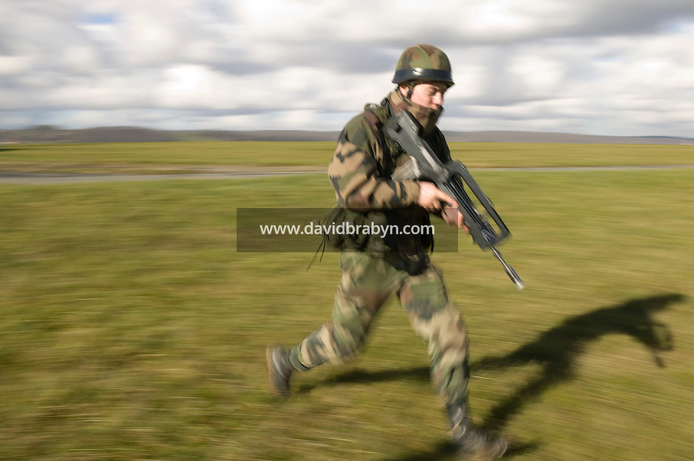 A member of the French Foreign Legion runs to his position after jumping over the airport of Tarbes, France, during a full scale multi-force exercise, 11 December 2007.