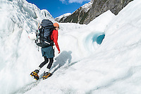 Female climber heading into small ice cave on Franz Josef Glacier, Westland National Park, West Coast, World Heritage Area, New Zealand
