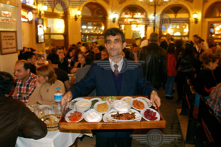 Restaurant waiter with tray loaded with dishes in the Cicek Pasaji (Flower passage) in the Beyoglu district. The passage contains many restaurants and bars (meyhanes - traditional taverns).