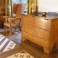 An Arts and Crafts leather wing-backed chair and detailed chest stand along a the wall of the living room