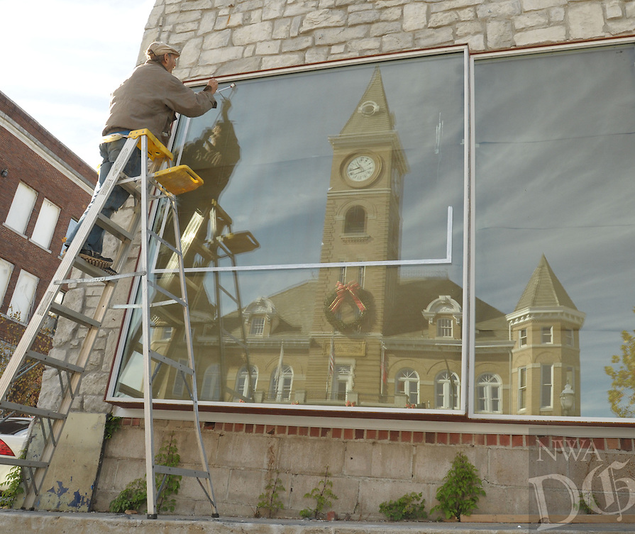 NWA Democrat-Gazette/ANDY SHUPE<br /> Longtime artist and sign painter Joe Alexander of Fayetteville paints a sign Friday, Nov. 6, 2015, for With, a new interior furnishings and fixtures store located at the corner of College Avenue and Center Street, as the historic Washington County Courthouse in Fayetteville is reflected in the store's window. Alexander is working on a series of paintings of classic cars with the intention of having a show when he is finished with the project.