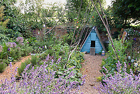Hen house, poultry bird chicken coop in cottage garden of catmint nepeta, ornamental onions Allium, herbs, flowers, brick wall, pebble mulch pathways, lavenders blues pu