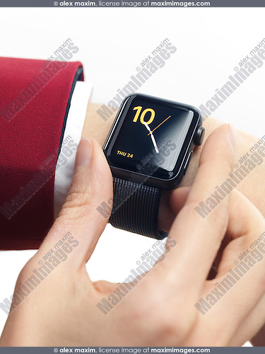 Woman hand in red suit with Apple Watch smartwatch on her wrist displaying clock isolated on white background
