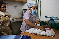 Nurse Sejal Parmar (center), 32, weighs and wraps a new born baby after a surrogate went into labor and gave birth unexpectedly in the Akanksha Infertility Center in Anand, Gujarat, India on 12th December 2012.  Photo by Suzanne Lee / Marie-Claire France